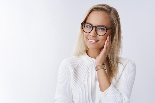 Photo d'intérieur d'une jeune femme d'affaires élégante, heureuse et heureuse, satisfaite d'une procédure cosmétique prenant des vitamines et des masques de soin de la peau touchant une peau de soie douce et souriant tendrement à la caméra sur un mur blanc.