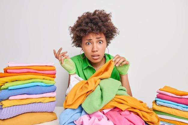 Photo d'intérieur d'une jeune femme afro-américaine perplexe qui choisit des vêtements pour laver plie le linge occupée à faire des tâches ménagères assise à table contre un mur blanc fait des tas de vêtements soignés