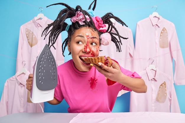 Une photo d'intérieur d'une jeune femme au foyer mord une délicieuse tarte vêtue d'un t-shirt rose décontracté tient le fer occupé à faire des poses de travaux ménagers contre le mur bleu