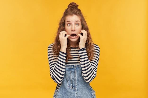 Photo d'intérieur d'une jeune femme aux longs cheveux roux, portant une salopette en jean et une chemise rayée, mettant en vedette à l'avant avec une expression faciale effrayée tout en regardant un film d'horreur