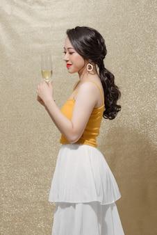 Photo d'intérieur d'une jeune femme séduisante et positive en robe de soirée avec une coupe de champagne,
