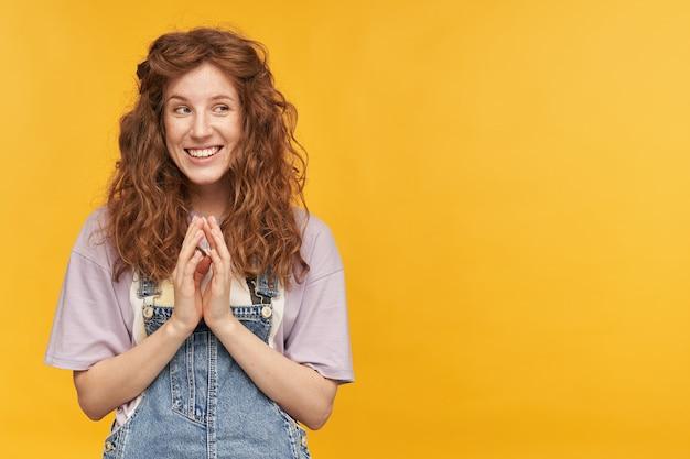 Photo d'intérieur d'une jeune femme souriante et heureuse, aux cheveux longs ondulés, garde sa paume ensemble, regarde de côté avec une expression faciale positive
