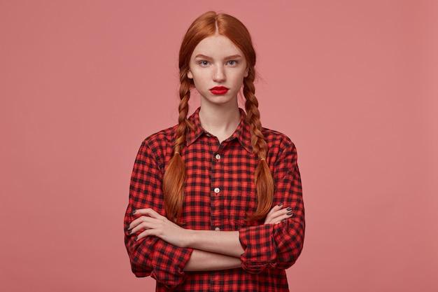Photo d'intérieur d'une jeune femme triste et confuse, garde la main croisée sur la poitrine, regarde directement dans la caméra avec une expression faciale négative, leva les sourcils