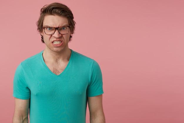 Photo d'intérieur d'un jeune homme brune, porte des lunettes et un t-shirt bleu, regarde directement dans la caméra avec une expression faciale négative folle