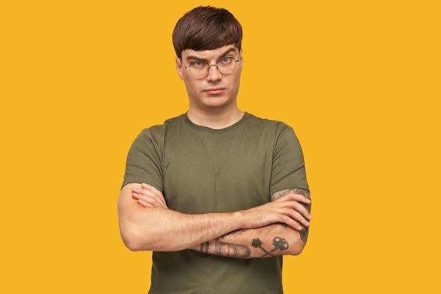 Photo d'intérieur d'un jeune homme regarde sérieusement à l'avant avec un sourcil levé, garde sa main croisée sur la poitrine avec une expression faciale confuse et mécontente