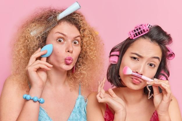 Photo d'intérieur de jeunes femmes multiethniques maquillant avec un pinceau cosmétique