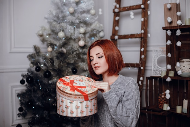 Photo d'intérieur de mode de la belle jeune femme aux cheveux rouges et au sourire charmant, porte un cardigan tricoté confortable, posant à côté de l'arbre de noël et présente un gâteau au chocolat avec des astérisques