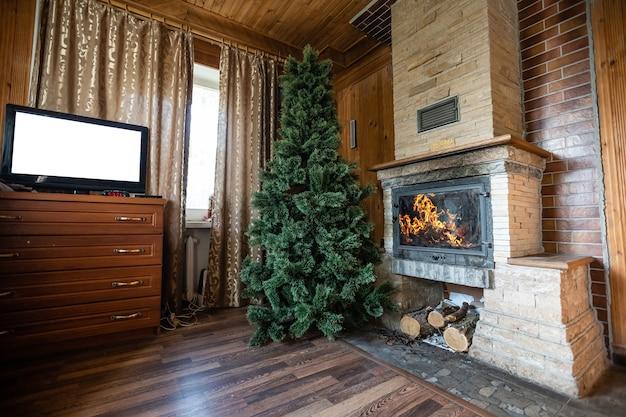 Photo de l'intérieur d'une pièce avec un mur en bois, un sapin de noël, une cheminée. ambiance de noël. confort à la maison