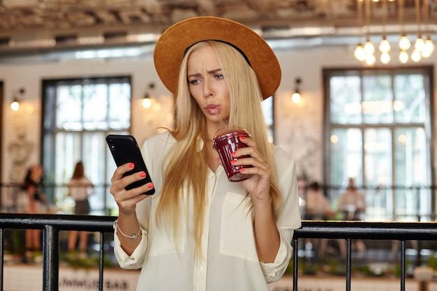 Photo intérieure de la belle femme confuse aux cheveux longs posant sur l'intérieur du restaurant avec une tasse de limonade à la main, en regardant son téléphone portable et en lisant des messages