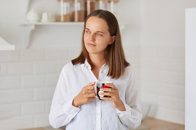 Photo intérieure d'une femme rêveuse aux cheveux noirs vêtue d'une chemise blanche tenant une tasse avec du café ou du thé, détournant les yeux avec une expression rêveuse, posant dans une cuisine lumineuse à la maison.