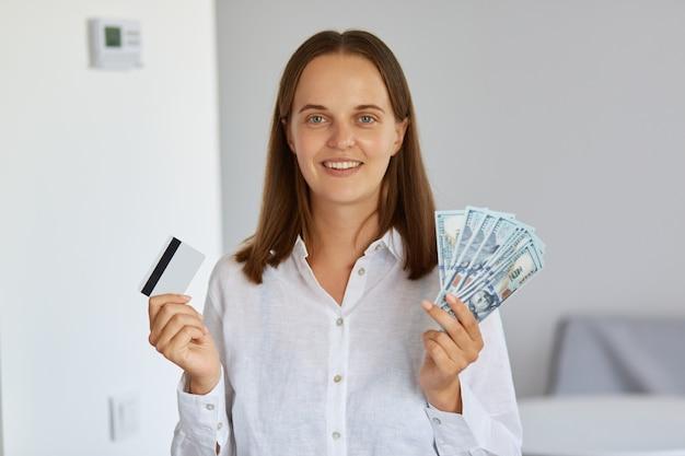 Photo intérieure d'une femme riche et positive heureuse debout dans une pièce lumineuse contre un mur blanc, tenant des billets de banque en dollars et une carte de crédit dans les mains, regardant la caméra, portant une chemise.