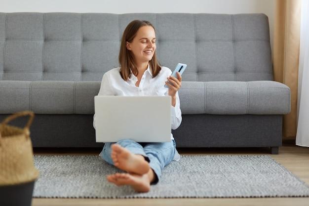 Photo intérieure d'une femme souriante portant une chemise blanche et un jean travaillant en ligne via un ordinateur portable à la maison, faisant une pause, vérifiant les réseaux sociaux, e-mail, utilisant un smartphone, assise par terre dans une pièce lumineuse.