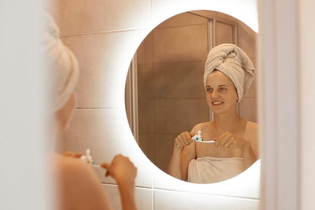 Photo intérieure d'une jeune femme adulte se brossant les dents dans la salle de bain, regardant son reflet dans le miroir, debout les épaules nues et une serviette blanche sur les cheveux.