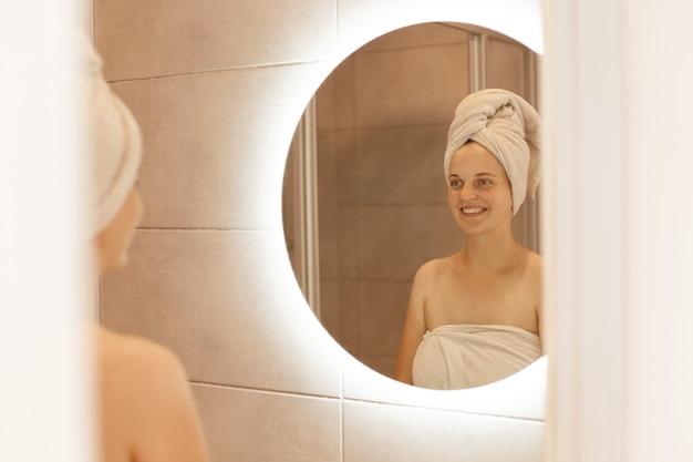 Photo intérieure d'une jeune femme adulte séduisante regardant le reflet dans le miroir après la douche et souriante, enveloppée dans une serviette blanche, exprimant des émotions positives.