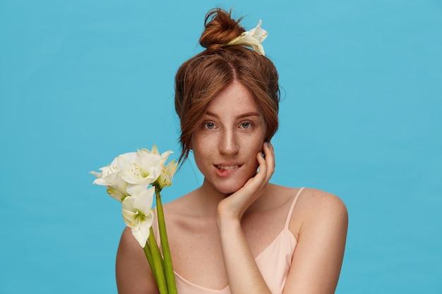 Photo intérieure d'une jeune femme rousse aux yeux verts tenant la main levée sur son visage et mordant la sous-couche tout en regardant doucement la caméra, debout sur fond bleu