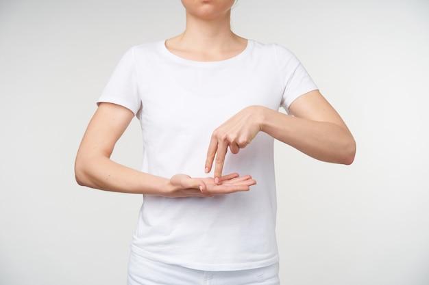 Photo intérieure de jeune femme tenant deux doigts sur la paume surélevée tout en utilisant la langue des signes pour exprimer ses pensées, isolé sur fond blanc
