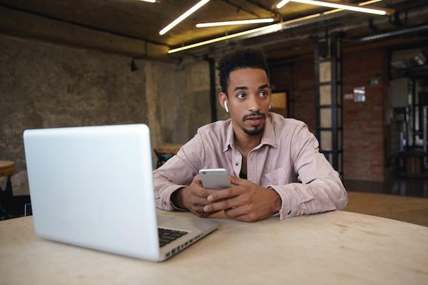 Photo intérieure d'un joli jeune homme à la peau sombre avec barbe assis à table avec ordinateur portable et tenant un téléphone portable dans les mains, regardant de côté avec un visage calme, portant des vêtements décontractés