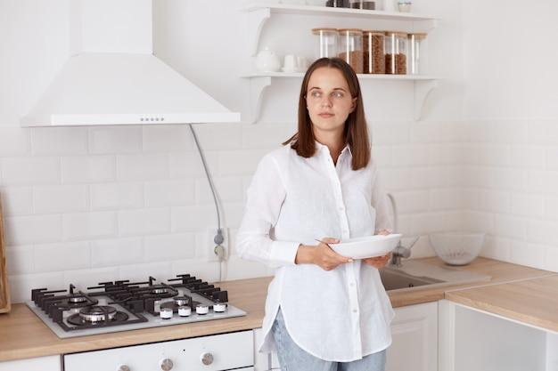 Photo intérieure d'une jolie jeune femme adulte aux cheveux noirs et pensive prenant son petit-déjeuner dans la cuisine, debout avec une assiette dans les mains, détournant les yeux avec une expression réfléchie.