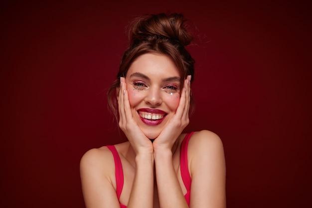 Photo intérieure d'une jolie jeune femme joyeuse avec une coiffure en chignon et un maquillage festif tenant son visage avec des paumes et souriant largement, debout en haut avec des sangles
