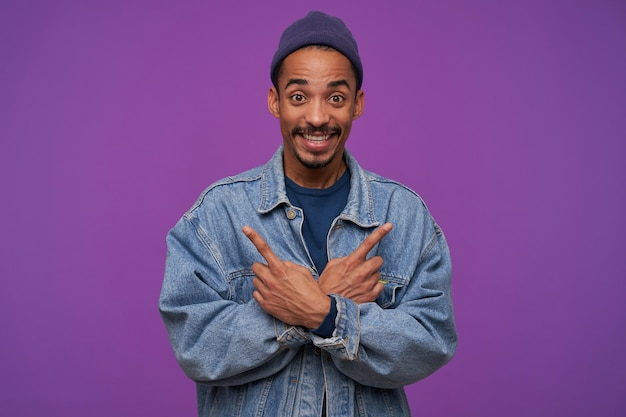 Photo intérieure de joyeux jeune homme barbu à la peau sombre et souriant largement tout en montrant avec l'index dans différentes directions, debout sur un mur violet