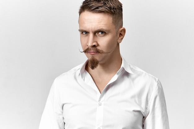 Photo isolée de beau jeune homme entrepreneur prospère avec moustache de guidon et barbiche posant en studio portant une chemise formelle blanche, regardant la caméra avec un sourire confiant