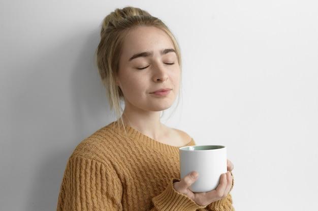 Photo isolée de la belle jeune femme portant un pull chaud confortable fermant les yeux avec plaisir, appréciant le café frais chaud, tenant une grande tasse