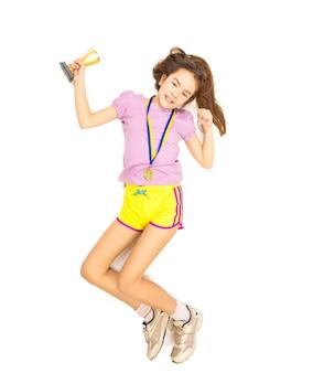 Photo isolée du point de vue élevé d'une fille heureuse sautant avec une coupe de trophée et une médaille d'or