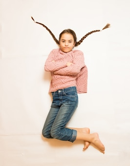 Photo isolée de fille triste avec de longues tresses allongé sur le sol