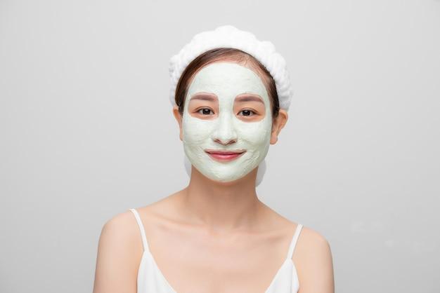Photo isolée d'une jolie femme portant un masque facial pour rafraîchir la peau avec sa serviette sur fond blanc.