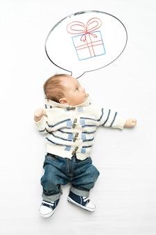 Photo isolée d'un mignon petit garçon rêvant de cadeau
