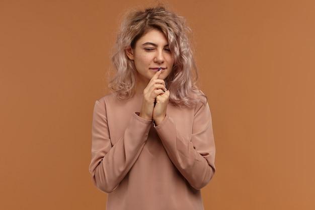 Photo isolée de mysteriousyoung femme européenne avec coupe de cheveux élégante regardant vers le bas avec une expression faciale pensif