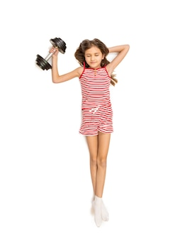 Photo isolée de petite fille soulevant des haltères lourds