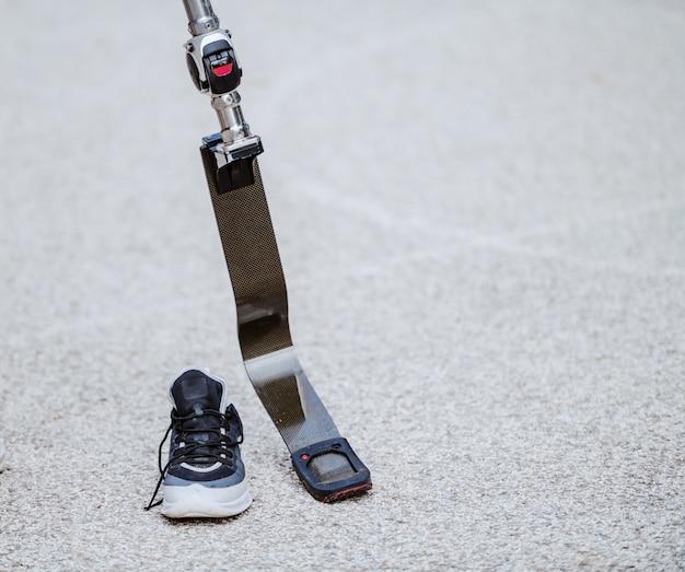 Photo d'une jambe artificielle et d'une sneaker à côté.