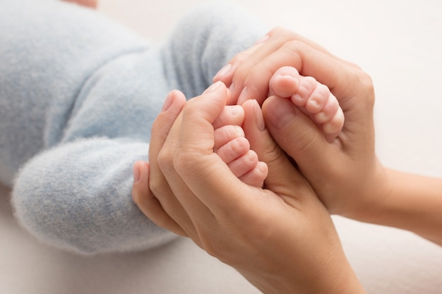 Photo avec des jambes d'enfants tenues dans les paumes de maman et papa. photo en noir et blanc. album de famille. photo de haute qualité