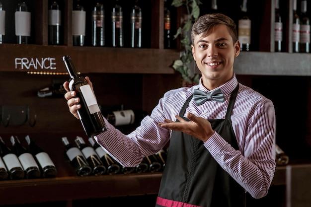 Photo d'un jeune barman souriant posant avec une bouteille ouverte