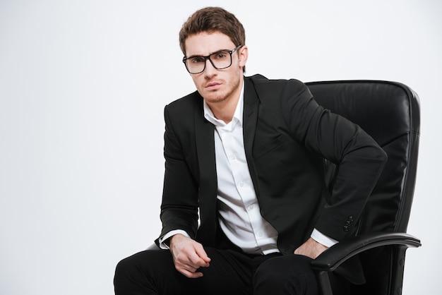 Photo de jeune bel homme d'affaires assis sur une chaise. isolé sur mur blanc.