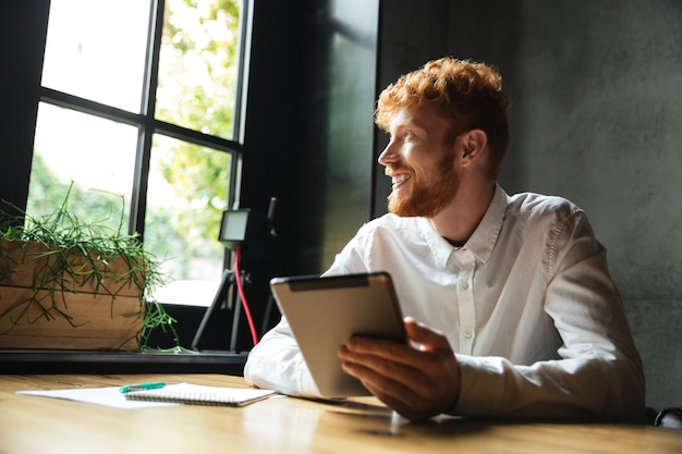 Photo de jeune bel homme barbu tête de lecture tenant la tablette, regardant la grande fenêtre