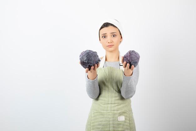 Photo de jeune belle femme au foyer tenant deux choux violets