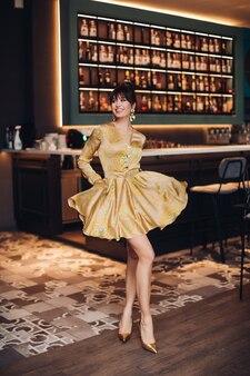 Photo de jeune belle femme caucasienne aux cheveux noirs en robe argentée et chaussures pose pour la caméra