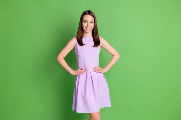 Photo de jeune belle fille fraîche et lumineuse dame regarder les mains de l'appareil photo côtés taille publicité vêtements marque concept modèle défilé porter une mini robe violette isolée fond vert couleur pastel