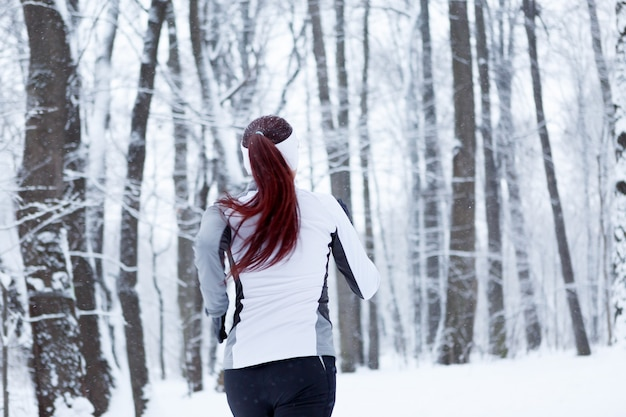 Photo d'une jeune brune fait du sport dans un parc d'hiver