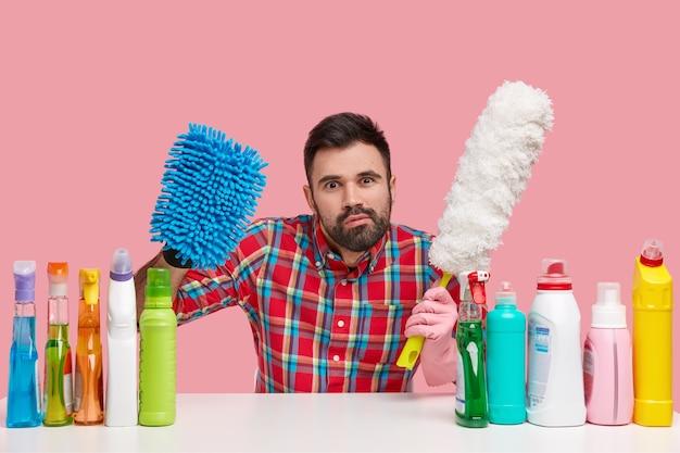 Photo d'un jeune concierge attentif regarde scrupuleusement, tient une éponge et une brosse à poussière, porte une chemise à carreaux rouge