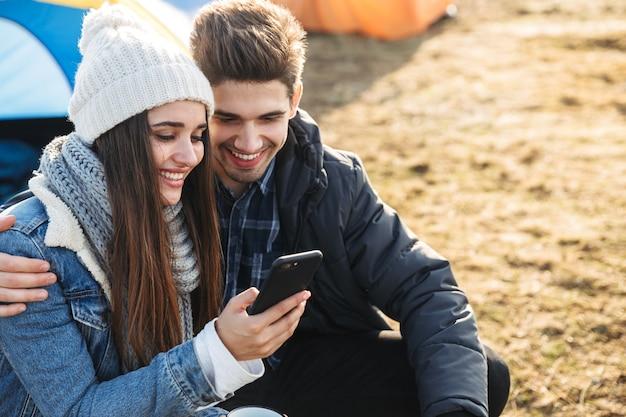 Photo d'un jeune couple d'amoureux heureux à l'extérieur avec tente en vacances alternatives gratuites en camping au-dessus des montagnes à l'aide d'un téléphone portable