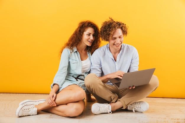 Photo de jeune couple de contenu homme et femme assis sur le sol et à l'aide d'un ordinateur portable d'argent, isolé sur fond jaune