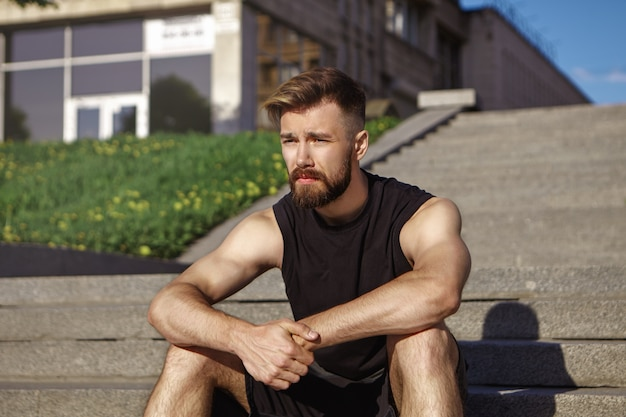 Photo de jeune coureur masculin épuisé réfléchi avec barbe floue et peau bronzée assis sur des marches de béton, se détendre après un entraînement cardio intensif concept de sport, de remise en forme, de style et de mode