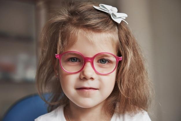 Photo de jeune enfant de sexe féminin aux cheveux blonds dans des verres roses assis dans le cabinet du médecin.