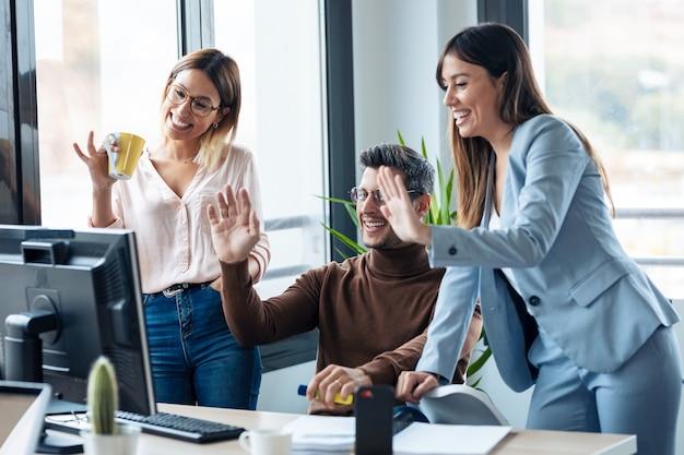 Photo d'une jeune équipe commerciale prospère debout autour d'un ordinateur en train de passer un appel vidéo dans l'espace de coworking.