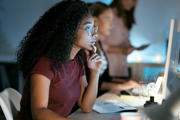 Photo d'une jeune femme d'affaires confiante travaillant avec un ordinateur portable assis au bureau.