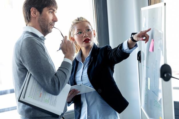 Photo d'une jeune femme d'affaires élégante pointant sur un tableau blanc et expliquant le projet à son collègue sur un lieu de coworking.