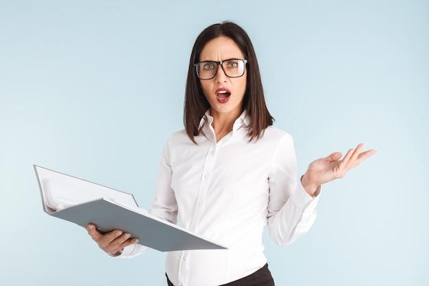 Photo d'une jeune femme d'affaires enceinte émotionnelle confuse isolé tenant le dossier.